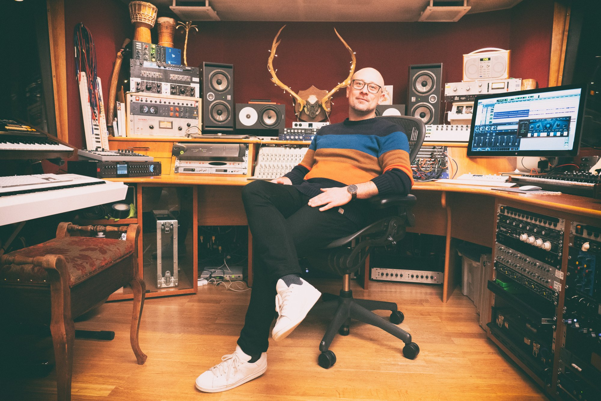 Producer Tom Fuller sitting on a chair in his studio The Cabin
